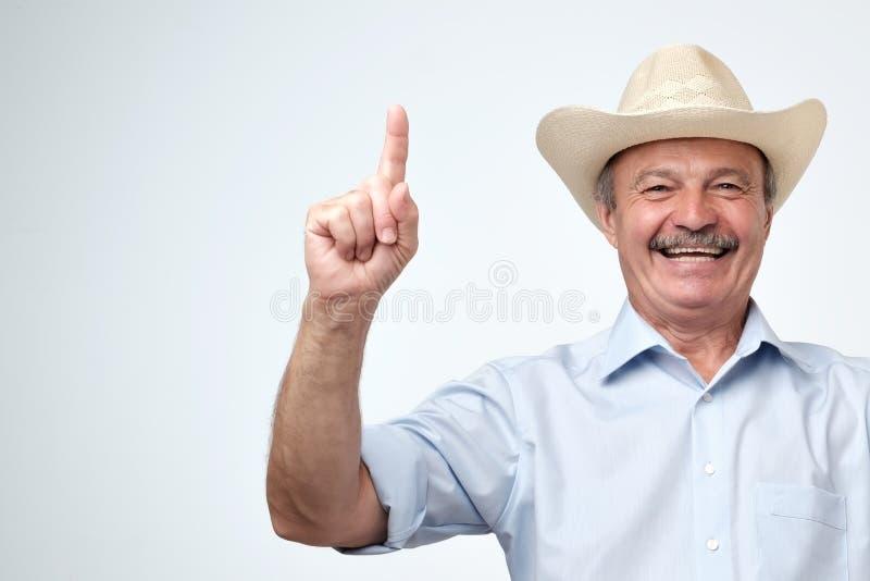 Votre faire de la publicité ici Portrait de studio d'homme supérieur bel dans le chapeau bleu de chemise et de cowboy montrant l' photos stock