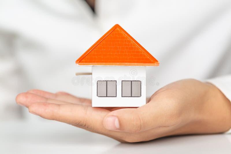 Votre nouvelle maison, mains de femme tenant une maison mod?le Hypoth?quez la maison mobile r?veuse d'assurance des biens et le c image stock