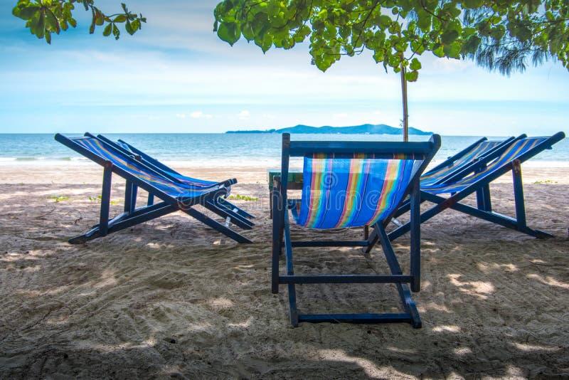 Vouwend stoel met blauwe kleur op het strand in zonlicht met overzeese mening/Aard en vakantie stock afbeelding