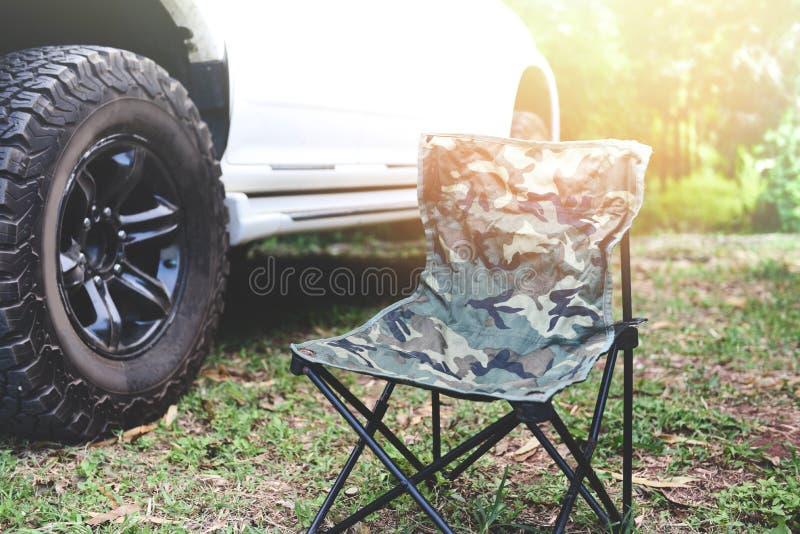 Vouwend stoel op het Kamperen met van wegbestelwagen en zonlichtachtergrond - Picknickstoel royalty-vrije stock fotografie