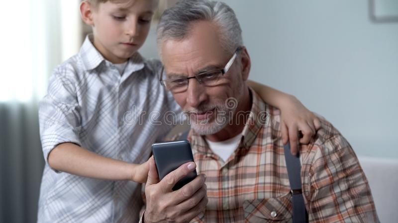Vovô do ensino do menino para usar o smartphone, nação digital contra a geração mais velha foto de stock royalty free