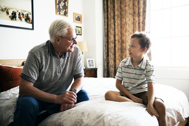 Vovô e neto que sentam-se na cama imagens de stock