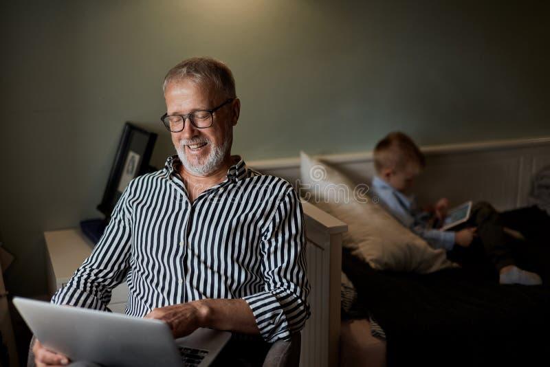 Vovô e neto que usa dispositivos e sorrindo ao passar o tempo que senta-se junto no sofá imagens de stock royalty free