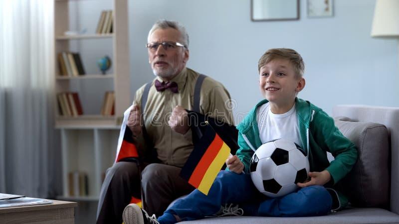 Vovô envolvido no futebol de observação da bandeira alemão com o menino, preocupando-se sobre o jogo fotografia de stock