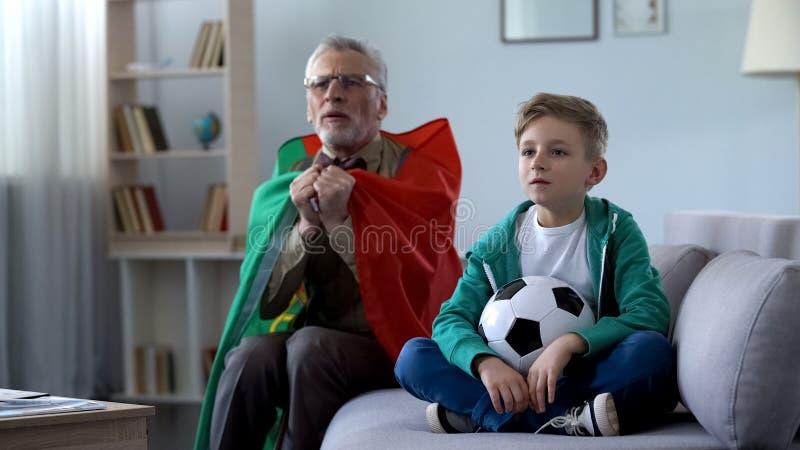 Vovô envolvido no futebol de observação da bandeira portuguesa com o menino, preocupando-se sobre o jogo imagens de stock royalty free