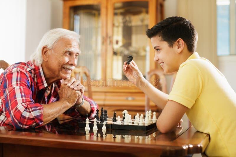 Vovô que joga o jogo de mesa da xadrez com neto em casa foto de stock