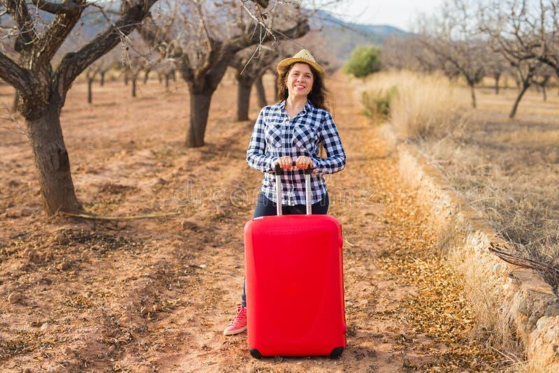 Voyage, été et concept de personnes - femme avec la valise rouge dans le chapeau au-dessus du fond de nature Elle est en vacances images stock