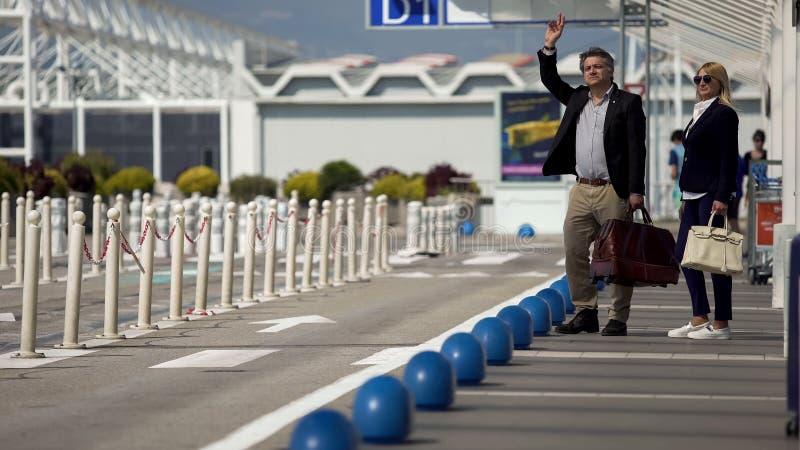 Voyage d'affaires, homme et taxi de salut de femme près d'aéroport, services de transport photos stock