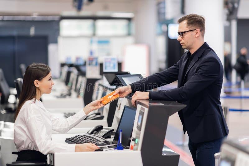 Voyage d'affaires Le jeune homme d'affaires beau dans le costume tenant son passeport et parlant ? la femme ? la ligne a?rienne v photographie stock libre de droits