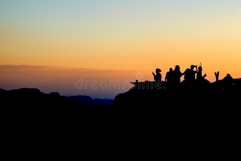 Voyage d'ami de groupe de silhouette à l'isolat de montagne avec le fond crépusculaire image stock