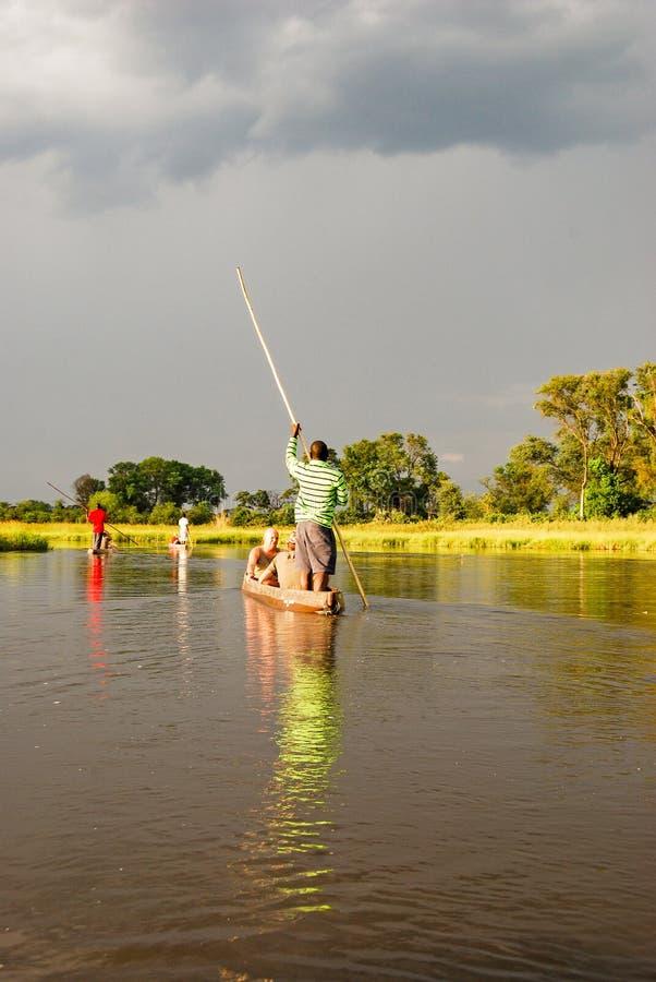Voyage de canoë avec le bateau traditionnel de mokoro sur la rivière par le delta d'Okavango près de Maun, Botswana Afrique image libre de droits
