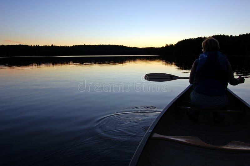 Voyage de coucher du soleil et de canoë photo stock
