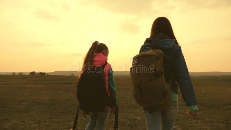 Voyage de maman et de fille avec un sac à dos contre le ciel Les touristes m?re et enfant vont au coucher du soleil dans les mont photographie stock