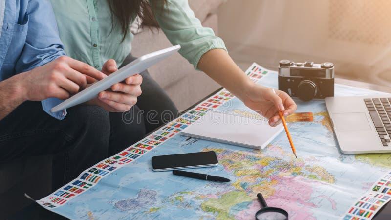 Voyage de planification Couplez discuter des plans de visite utilisant la carte photos stock