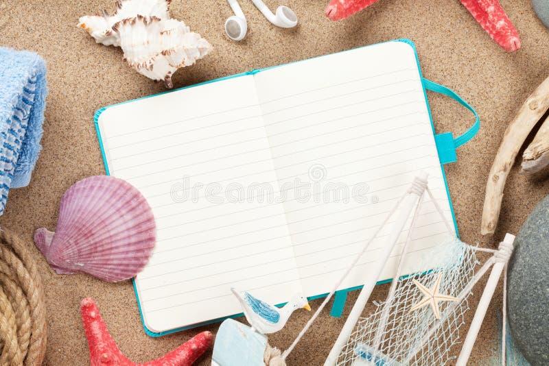 Voyage et bloc-notes de vacances avec des articles au-dessus du sable photos libres de droits