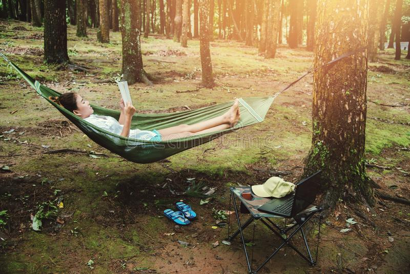 Voyage naturel de femmes asiatiques d?tendre pendant les vacances sommeil lisant un livre dans l'hamac camper sur le parc nationa photo stock