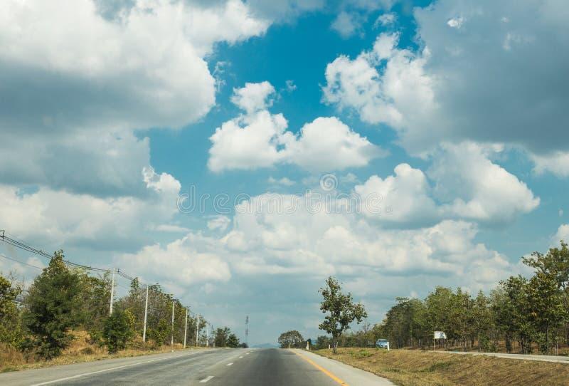 Voyage par la route à hors de la ville avec des lignes des arbres verts et du ciel bleu de nuages gentils en été image stock