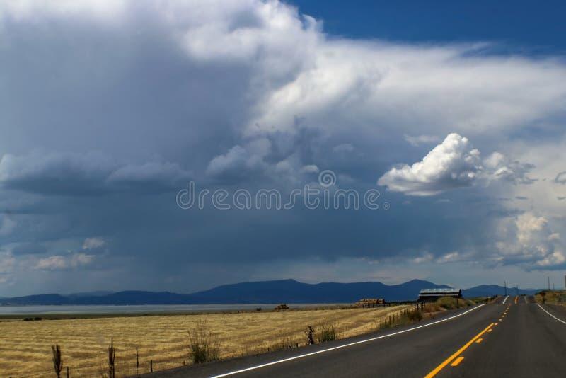 Voyage par la route - tronçons à deux voies supérieurs noirs de route au-dessus de l'horizon après un champ de grange et de foin  photographie stock libre de droits