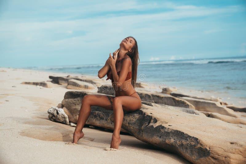 Voyage, pays tropicaux, récréation, concept de mode de vie La jeune belle fille s'assied sur le rivage de la mer bleue images libres de droits