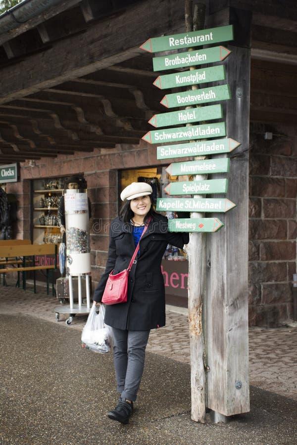 Voyage thaïlandais asiatique de femme et pose avec le panneau de guide d'information image stock