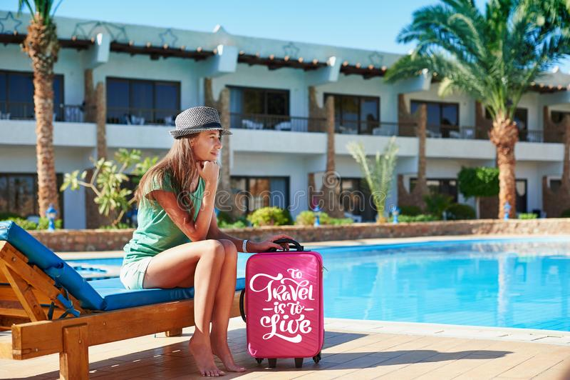 Voyage, vacances d'été et concept de vacances - belle femme marchant près de l'espace piscine d'hôtel avec la valise rouge en Egy image stock