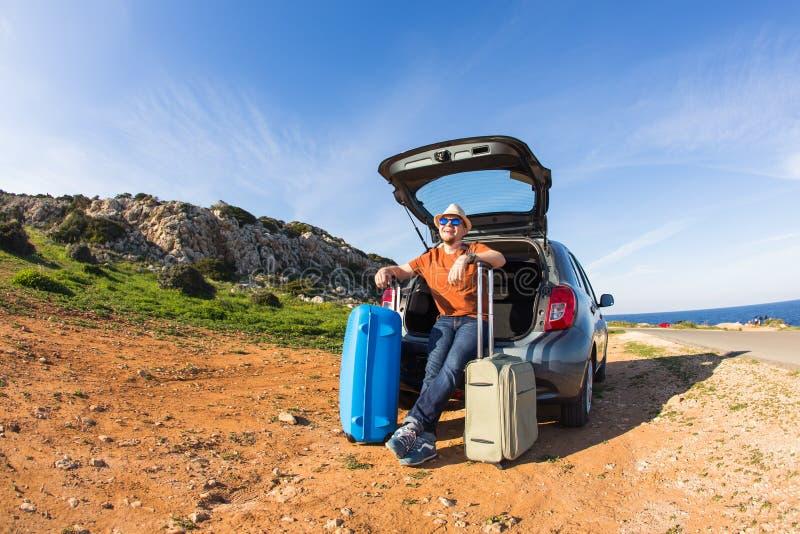 Voyage, vacances, voyage d'été et concept de personnes - l'homme part en vacances, valises dans le tronc d'une voiture image libre de droits