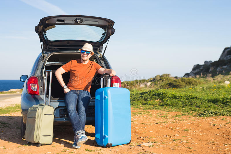 Voyage, vacances, voyage d'été et concept de personnes - l'homme part en vacances, valises dans le tronc d'une voiture photos stock
