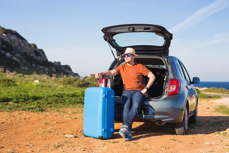 Voyage, vacances, voyage d'été et concept de personnes - l'homme part en vacances, valises dans le tronc d'une voiture photos libres de droits