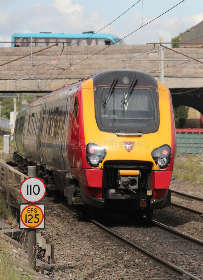 Voyager dmu on West Coast mainline at Carnforth. Voyager diesel multiple unit train in Virgin livery on the down line on the West coast main line (WCML) passing stock image