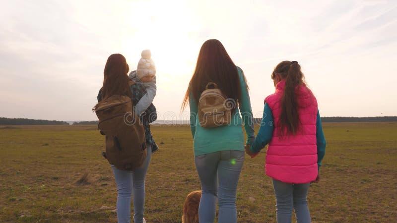 voyages de famille avec le chien sur la plaine travail d'?quipe d'une famille tr?s unie mère, petit enfant et filles et animaux f image libre de droits