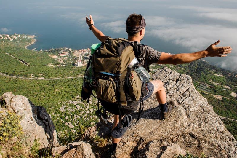 Voyageur avec un sac à dos de touristes, supports sur une montagne rocheuse photo stock