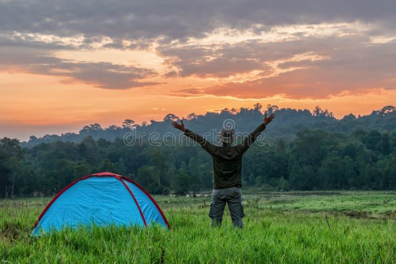 Voyageur ayant le camping avec la tente sur le champ d'herbe dans le matin du lever de soleil images stock