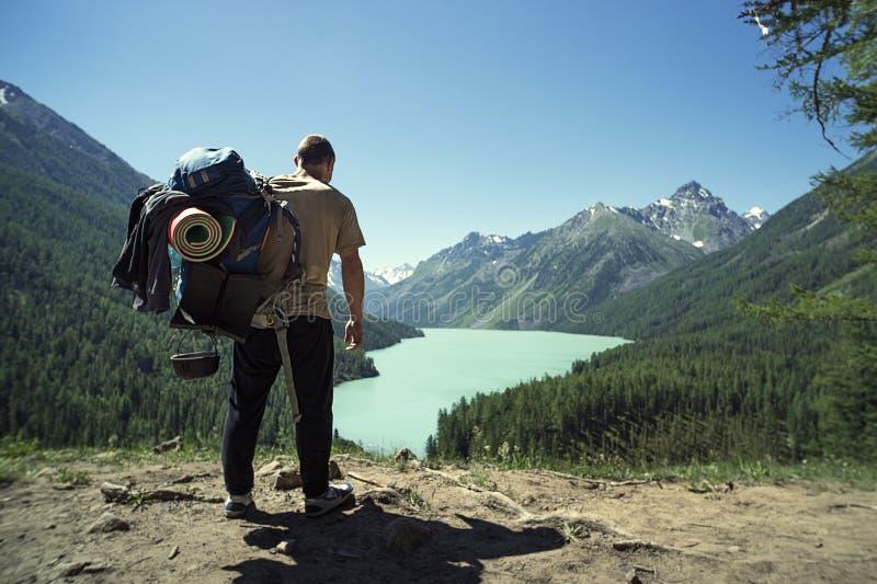 Voyageur d'homme avec le grand lac de concept de mode de vie de voyage d'alpinisme de sac à dos et montagnes les vacances o d'ext photo stock