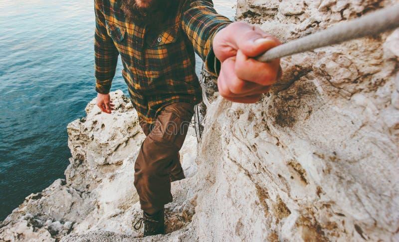Voyageur d'homme s'élevant tenant la corde au-dessus de la mer images libres de droits