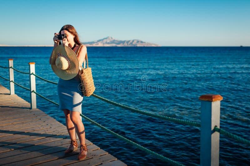 Voyageur de jeune femme prenant des photos de paysage de mer sur la jetée utilisant la caméra Mode d'été images libres de droits