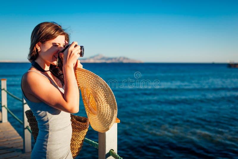 Voyageur de jeune femme prenant des photos de paysage de mer sur la jetée utilisant la caméra Mode d'été image stock