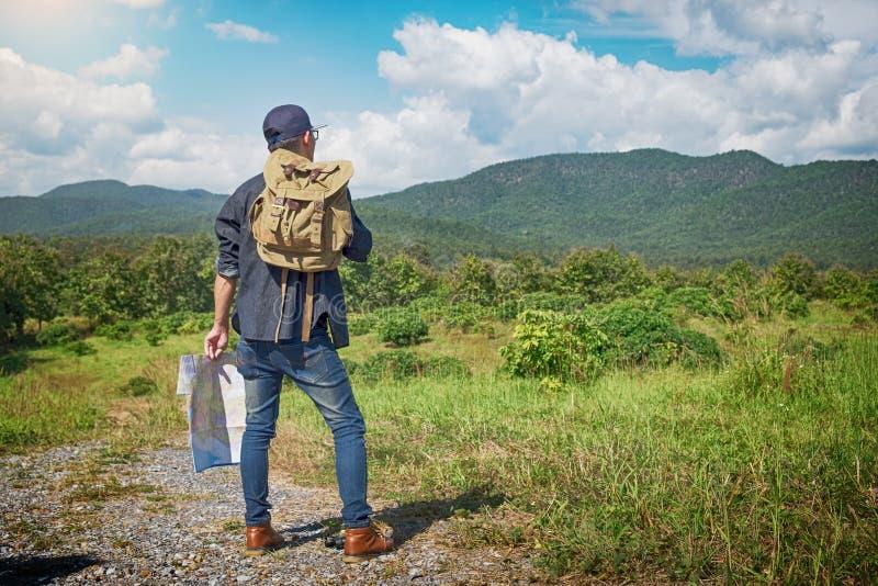 Voyageur de jeune homme avec la détente de sac à dos de carte extérieure avec rocheux photographie stock