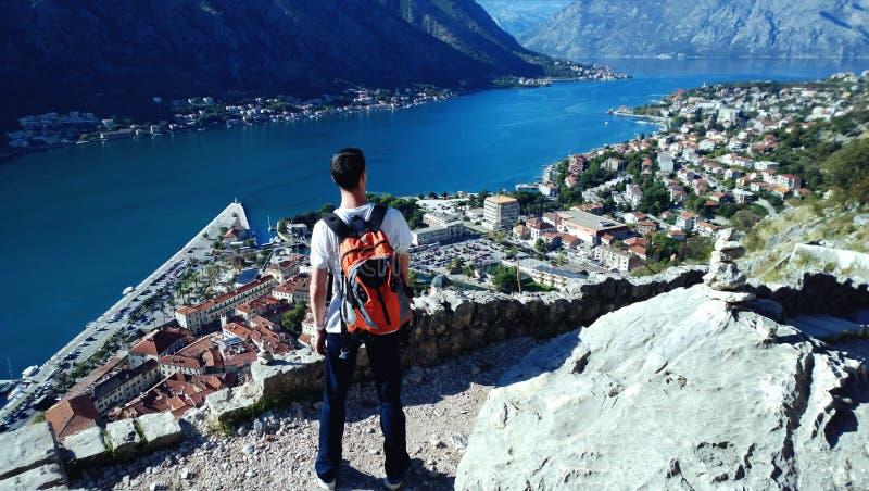 Voyageur de jeune homme avec le sac à dos orange appréciant la vue de la baie de Boka images stock