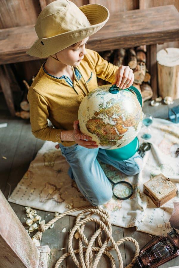 Voyageur de petit garçon dans le chapeau tenant le globe tout en se reposant sur le porche image libre de droits