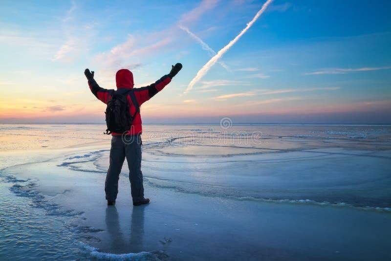 Voyageur de photographe de nature sur le lac congelé pendant le lever de soleil en hiver photographie stock libre de droits