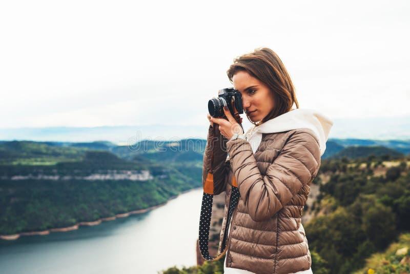 Voyageur de photographe sur le dessus vert sur la montagne, participation de regard de touristes dans la caméra numérique de phot photos stock