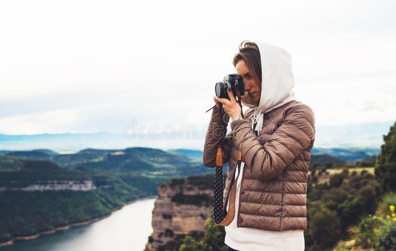 Voyageur de photographe sur le dessus vert sur la montagne, participation de regard de touristes dans la caméra numérique de phot photo stock