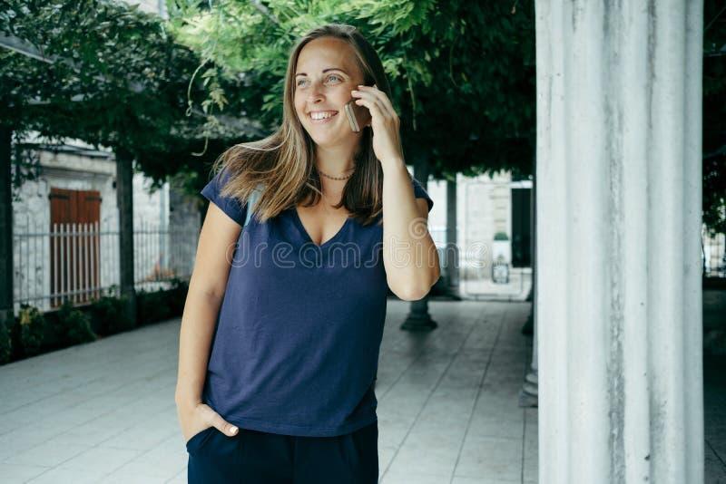 Voyageur de portrait de femme dans un T-shirt bleu avec un talkin de sac à dos photographie stock