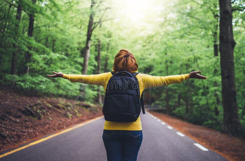 Voyageur de touristes avec le sac à dos se tenant avec les mains augmentées, vue de randonneur de fille de regarder arrière dans  image libre de droits