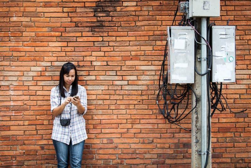 Voyageur féminin à l'aide du téléphone près du poteau et du mur de briques électriques photo stock