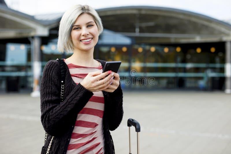 Download Voyageur Féminin De Sourire à L'aide Du Téléphone Intelligent En Dehors De La Station De Train Image stock - Image du personne, heureux: 77157861