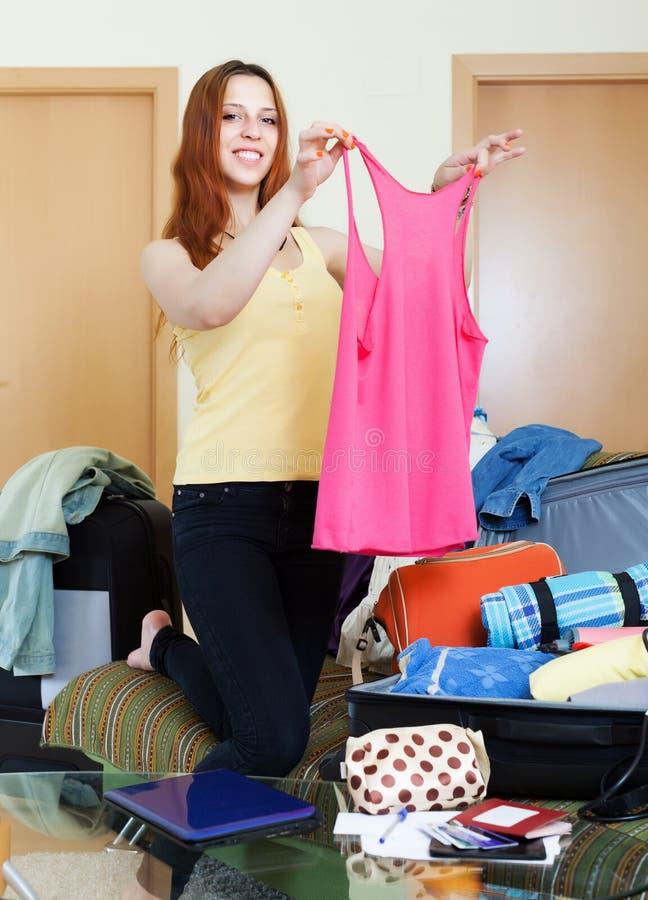 Voyageur féminin heureux choisissant des vêtements image libre de droits