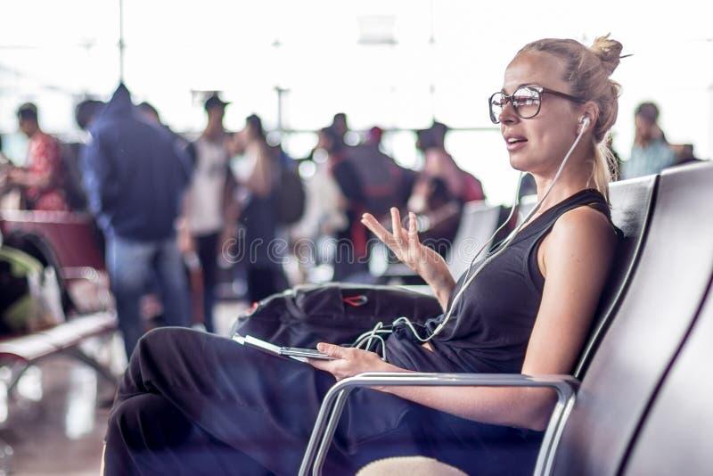 Voyageur féminin parlant au téléphone portable tout en attendant pour monter à bord d'un avion aux portes de départ sur le termin photographie stock