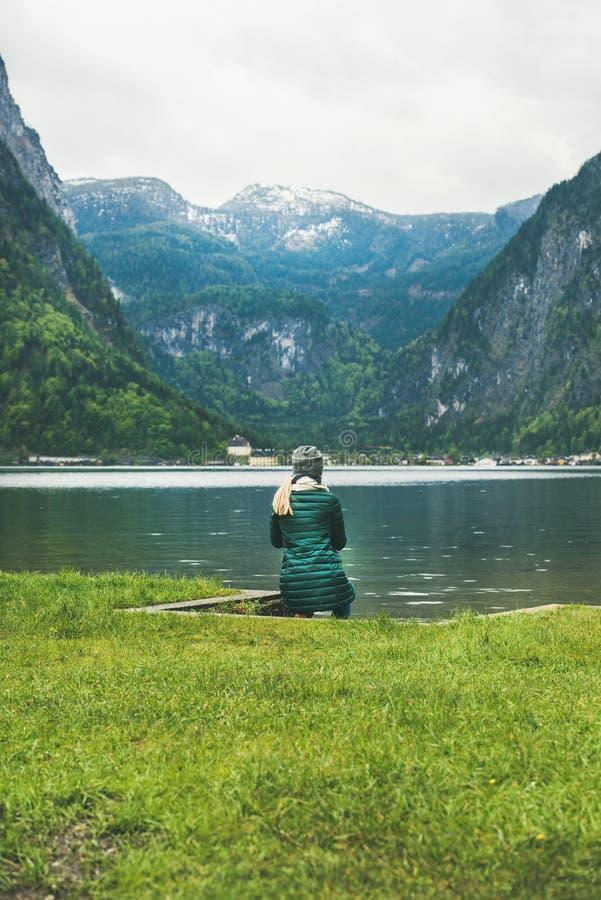 Voyageur féminin s'asseyant à la côte de lac de montagne dans les Alpes photos libres de droits