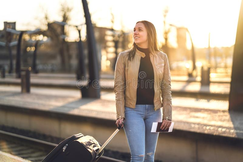 Voyageur féminin se tenant dans la plate-forme de train au coucher du soleil photo libre de droits